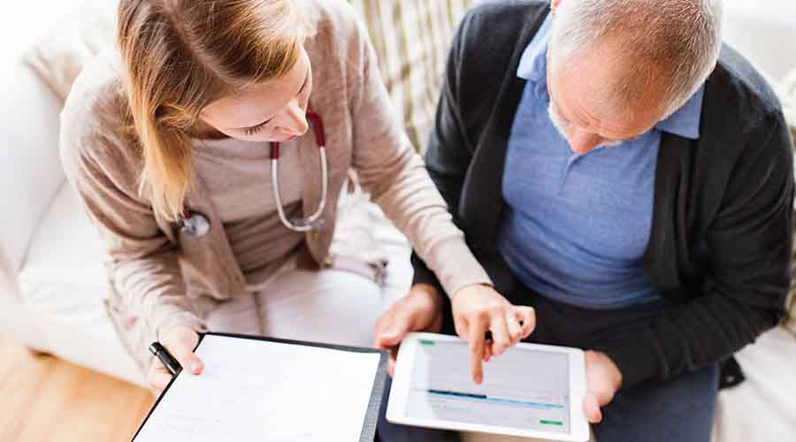 Doctor on a home call consulting patient's file using a tablet